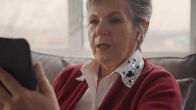 Señora mayor que habla con los amigos que usan su celular almacen de video