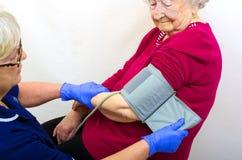 Señora mayor que hace la presión de la sangre comprobar Imágenes de archivo libres de regalías