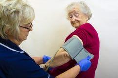 Señora mayor que hace la presión de la sangre comprobar Imagen de archivo libre de regalías
