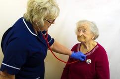 Señora mayor que hace la presión de la sangre comprobar Fotos de archivo