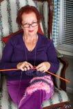 Señora mayor que le mira mientras que hace punto Fotos de archivo