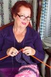 Señora mayor que le mira mientras que hace punto Imagen de archivo libre de regalías