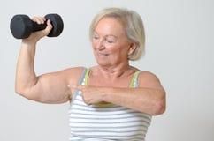 Señora mayor que lleva a cabo una pesa de gimnasia fotos de archivo libres de regalías