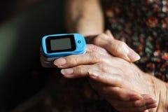 Señora mayor que mide su saturación del oxígeno con un oxímetro del pulso imágenes de archivo libres de regalías