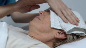Señora mayor que miente en el sufrimiento de la cama de la fiebre, enfermera que pone la toalla mojada en la frente almacen de video