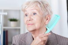Señora mayor que peina el pelo imágenes de archivo libres de regalías