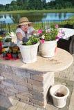 Señora mayor que prepara los potes de la planta ornamental Imágenes de archivo libres de regalías