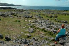 Señora mayor que se sienta en la roca que mira la opinión del mar Fotografía de archivo libre de regalías