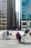 Señora mayor que se sienta en la tabla que mira una Nueva York foto de archivo libre de regalías