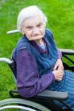 Señora mayor que se sienta en silla de ruedas Foto de archivo libre de regalías