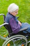 Señora mayor que se sienta en silla de ruedas Foto de archivo
