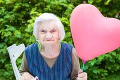 Señora mayor que sostiene un globo en forma de corazón Fotografía de archivo