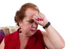 Señora mayor que sufre de un dolor de cabeza Fotos de archivo