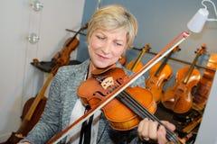 Señora mayor que toca el violín imagen de archivo