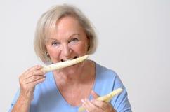 Señora mayor sana feliz con un espárrago blanco Foto de archivo libre de regalías