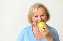Señora mayor sana feliz con una manzana verde Foto de archivo
