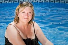 Señora mayor Sitting por la piscina Foto de archivo libre de regalías