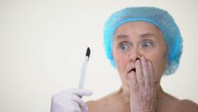 Señora mayor sonriente asustada del escalpelo quirúrgico, miedo del tratamiento, cirugía plástica metrajes