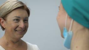 Señora mayor sonriente que abraza a la enfermera, remisión después de la enfermedad fatal, buenas noticias almacen de metraje de vídeo