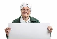 Señora mayor sonriente que sostiene la hoja en blanco en manos Imagenes de archivo
