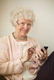 Señora mayor Using Her Cellphone a mandar un SMS imagenes de archivo
