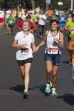 Señora mayor y mujer que corren llevando a cabo la mano Competencia de deporte Imágenes de archivo libres de regalías