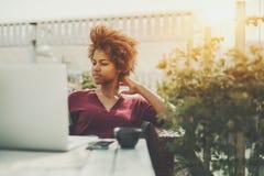 Señora mezclada pensativa rizada con el ordenador portátil en café al aire libre Imágenes de archivo libres de regalías