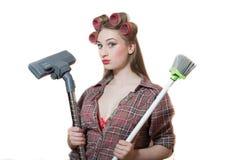 Señora modela en bigudíes con la aspiradora y la escoba imagenes de archivo