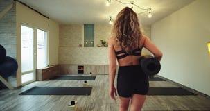Señora moderna del estudio de la yoga que entra comenzar su meditación de la yoga a celebrar en las manos su estera y llevar del  almacen de video