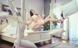 Señora morena atractiva que eleva y mantiene flotando en su dormitorio Foto de archivo libre de regalías