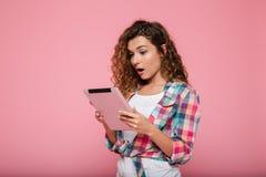 Señora morena caucásica joven que usa la tableta aislada sobre rosa Fotografía de archivo libre de regalías