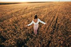 Señora morena hermosa en campo de trigo en la puesta del sol foto de archivo libre de regalías