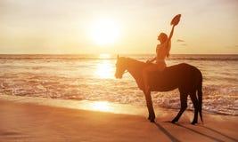 Señora morena que monta un caballo junto a la costa costa Imagenes de archivo