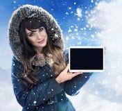 Señora morena que presenta un exterior de la tableta - invierno, día desapasible fotos de archivo