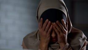 Señora musulmán frustrada en el hijab que cubre la cara con las manos, problemas de la vida, tensión fotos de archivo