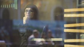 Señora musulmán pacífica feliz en el café que se sienta cerca de la ventana, pareciendo exterior, libertad almacen de video