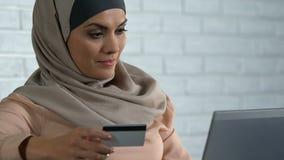Señora musulmán satisfecha que inserta el número de tarjeta de crédito en la PC del ordenador portátil, haciendo compras en línea metrajes