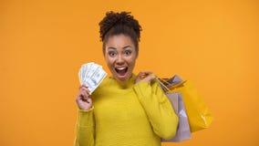 Señora negra emocional que lleva a cabo el manojo de dólares y de bolsos de compras, devolución de efectivo almacen de video