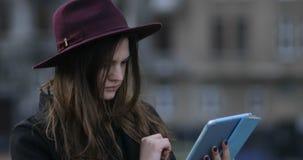 Señora noir moderna europea sonriente de los jóvenes que usa la tableta en el parque con su smartphone, 4k metrajes