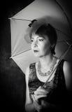 Señora pensativa con un paraguas Foto de archivo