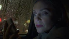 Señora pensativa en libro de lectura del taxi en el smartphone, uso en línea, charlando almacen de metraje de vídeo