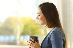 Señora pensativa que sostiene una taza de café al lado de una ventana Imagenes de archivo