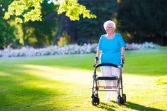 Señora perjudicada mayor con un caminante en un parque Fotografía de archivo