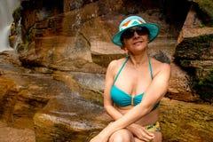 Señora preciosa Relaxing en una cascada imagen de archivo
