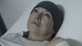 Señora presionada en la bufanda que miente en cama sin la esperanza de la recuperación, tratamiento contra el cáncer almacen de metraje de vídeo
