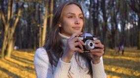 Señora que admira otoño a través de la lente de cámara del vintage y que intenta capturar el momento almacen de metraje de vídeo
