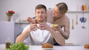 Señora que alimenta juguetónamente al marido con la rebanada del plátano, frutas como vitaminas sabrosas metrajes