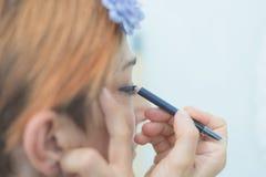 Señora que aplica lápiz de ojos azul en el párpado Imagenes de archivo