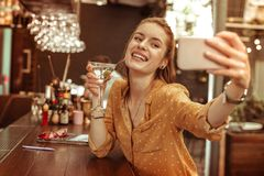 Señora que brilla intensamente que toma selfies mientras que estando en la barra con una bebida imagenes de archivo