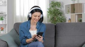 Señora que busca y que escucha la música en el teléfono almacen de metraje de vídeo